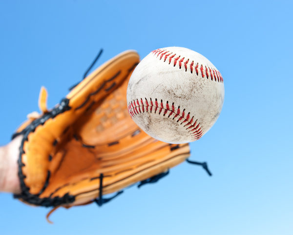 Person catching baseball with blue sky background