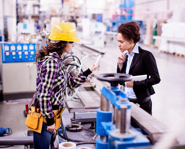 Girl in a factory working with her woman boss