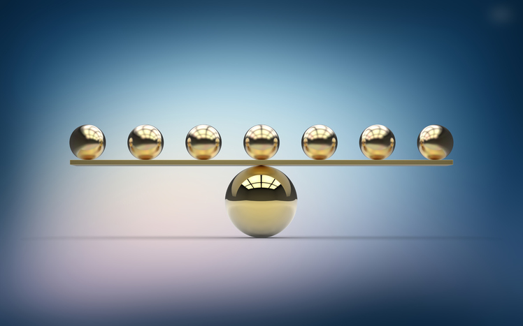 Seven gold balls balancing on one large gold ball