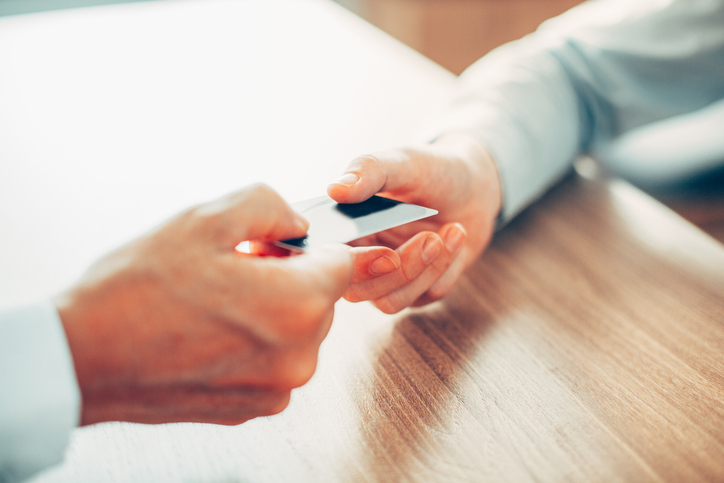 Close-up of male hand giving credit card_tone
