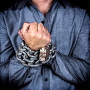 Hands of a formally dressed man chained together