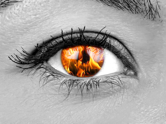 Closeup female eye iris burning
